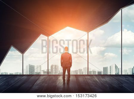 Businessman standing on the floor back to us looking through the big window with cityscape and sunset behind it. Business and management. Looking to the future. City and people.