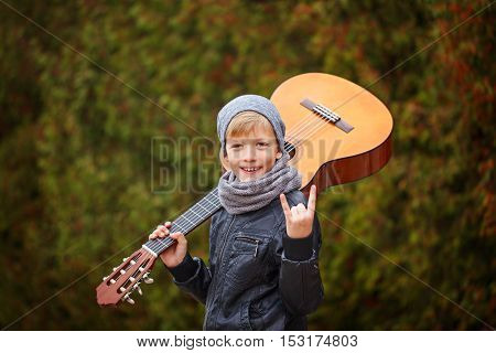 Portrait of adorable young boy with guitar on nature background. Kid shows the rock and roll gesture