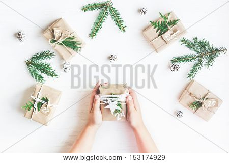 Christmas calendar. Christmas gift fir branches pine cones. Child's hands. Flat lay top view