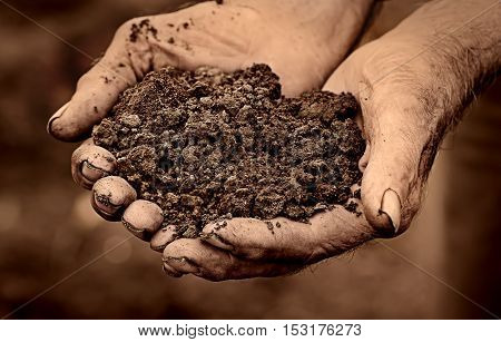 Dramatic photo of an elderly man holding soil in hands