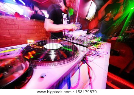 DJ behind the decks in a nightclub. DJ spinning plate. people dancing in a nightclub. disco