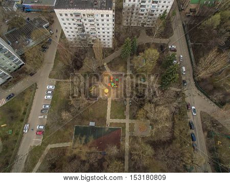 Aerial view of multistorey blocks of flats and yard with playground and sports ground. Moscow, Russia