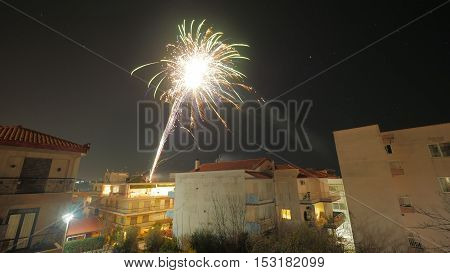 Holiday celebration with night fireworks over the houses in small town