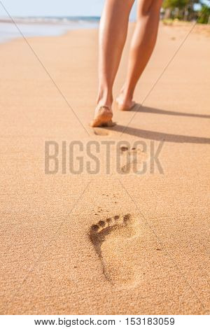 Beach sand footprints woman feet walking barefoot. Travel girl relaxing walking on golden sand beach leaving footprints in the sand. Closeup detail of female feet and legs at sunset.