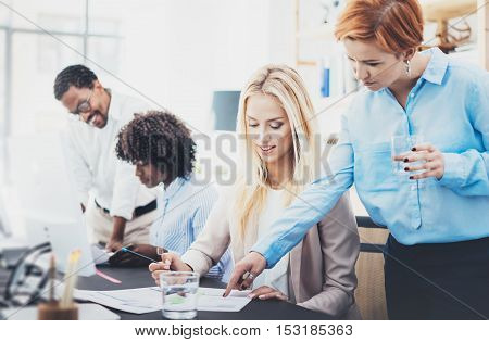 Group of four young coworkers discussing business plans in an office.Young business people making great business ideas. Horizontal, blurred background
