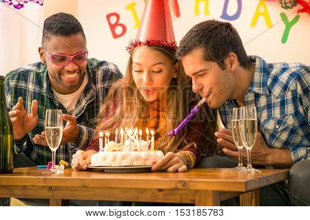 Girl 18th birthday party with happy multiracial friends - Young woman blowing on cake candles in festive moment together - Concept of friendship joy and the coming of legal age
