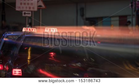 Taxi cars on night road, motion shot with trail from illuminated cab sign. Hong Kong