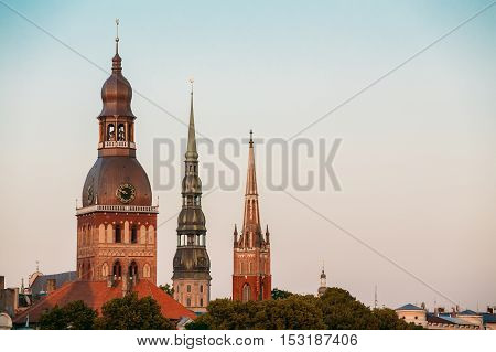 Riga, Latvia. Close View Of Three Towers With Steeples Of Riga Cathedral, St. Peter's Church And St. Saviour's Anglican Church In Old Town In Summer Under Blue Sky.