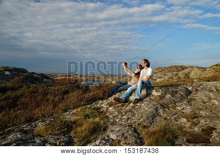Couple taking a selfie on large stone covered with colorful lichens at a coastal heathland at a hiking path next to Marstrand,  Kungälv Municipality, Västra Götaland County, Sweden