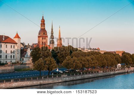 Riga, Latvia. The View Of 11 November Embankment Of River Daugava. The Towers, Steeples Of Riga Cathedral, St. Peter's Church And St. Saviour's Anglican Church In Old Town In Summer Under Blue Sky.
