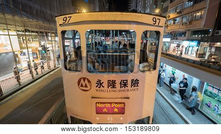 HONG KONG - NOVEMBER 09, 2015: Double-decker tramway making a stop in the street at night. Trams in Hong Kong have been a form of commuter transport for over 110 years