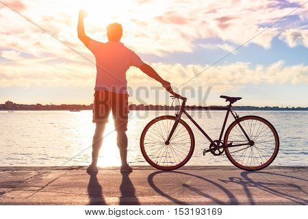 Happy man silhouette raising fist at sunset and holding sport bike - Young successful guy standing arm up to the sky celebrating goal achievement outdoors - Concept of happiness and human joy