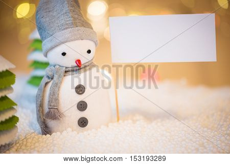 Cute festive snowman with sign Christmas lights in background