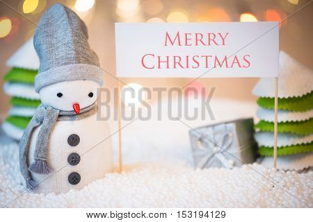 Cute festive snowman with Merry Christmas sign Christmas lights in background