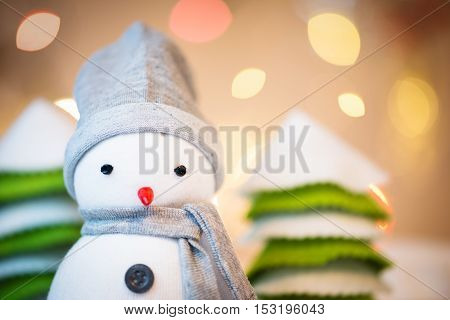 Detail of cute festive snowman with Christmas lights in background