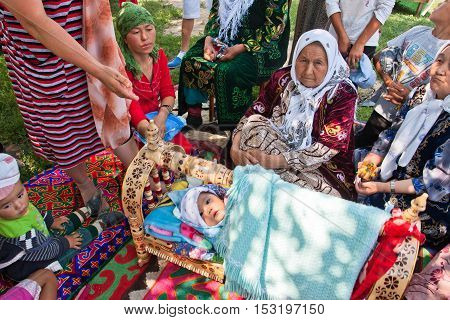 KEMIN, KYRGYZSTAN - AUGUST 2, 2013: Elderly village women tell the story of folk traditions of childbirth on August 2, 2013 in Kyrgyzstan. Central Asian Kyrgyzstan has population near 5.4 million