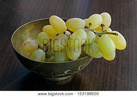 Small bunch of white grapes in brass bowl