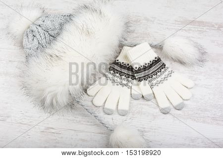 Winter hat with fur and knitted gloves on white wooden background