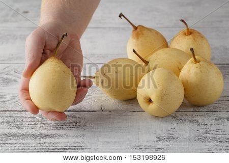 pears on wood table closeup in male hand