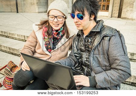Multiracial couple having fun using laptop - Modern concept of connection with computer technology - City urban lifestyle and everyday life rapport - Main focus on girl with warm desaturated filter