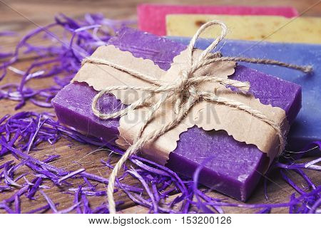 Collection of handmade, natural organic soap on wooden background. Spa products. Purple and vintage tinted