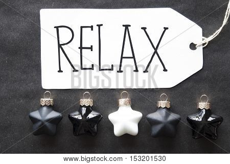 Label With English Text Relax. Black And White Christmas Tree Balls On Black Paper Background. Christmas Decoration Or Texture. Flat Lay View