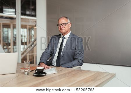 Portrait of a confident mature businessman in a suit sitting at a table with paperwork in an office boardroom