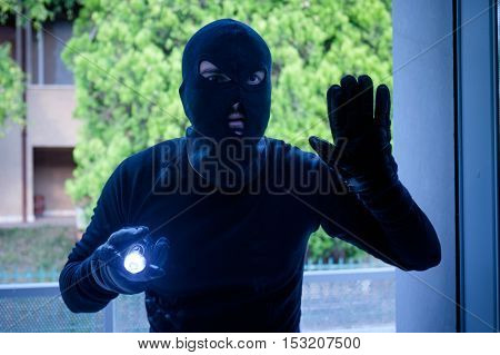 Burglar Wearing A Balaclava Looking Through The House Window