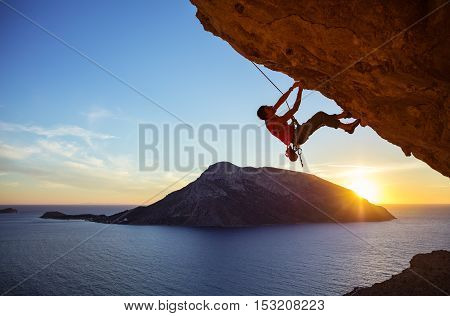 Male climber on overhanging rock against beautiful view of coast below