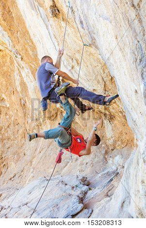 Two male climbers hanging on a rope. After a heavier leader fell off the cliff a lighter belayer (in a red vest) was pulled into the air.