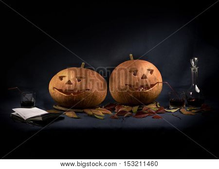Halloween pumpkins drinking wine at black background