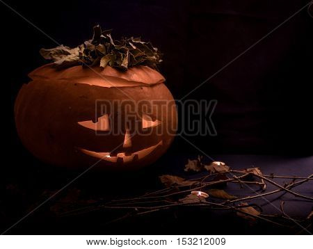 scary halloween pumpkin with candles glowing in the woods