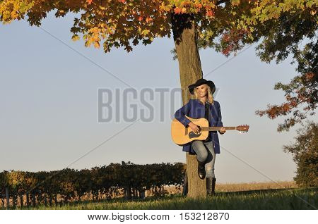 Beautiful asian mixed-race woman playing guitar outside during fall season