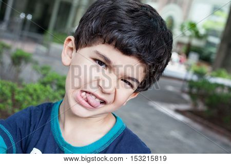 Boy grimacing shows tongue and teeth on park