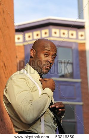 Sharp looking African American businessman fixing his necktie