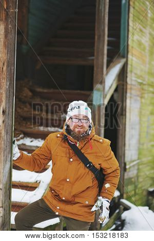 Funny attractive bearded man with glasses standing next to the old wooden house in snowy weather in the winter.