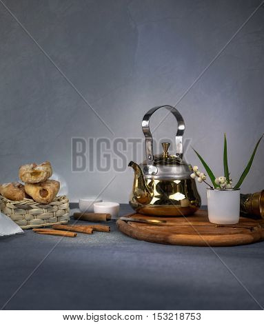 metal tea, cakes and vanilla on dark background
