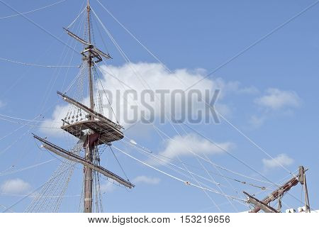 foreground of mast and crows nest of a ship with sky in the background