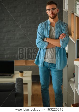 Young man standing near wall in office