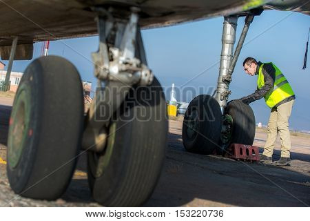 Male engineer checking airplane's wheels before flight
