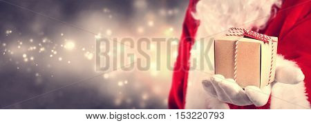 Santa Claus holding a gift in his hand