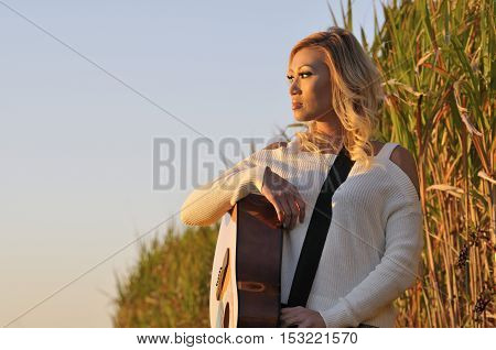 Portrait of beautiful asian woman with guitar at sunset