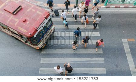 the bus is going at the crosswalk with people are walking in top view (aerial photo)