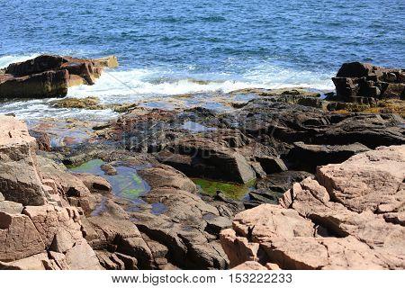 Waves crashing against rocks along the coast of Maine.