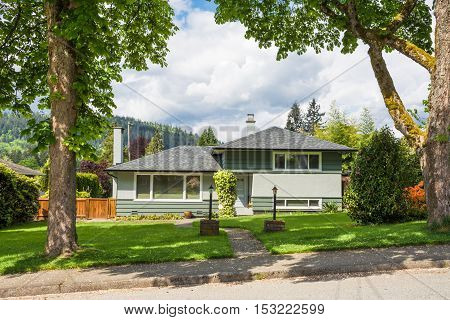 Family house with landscaped front yard on cloudy sky background. Residential house concrete pathway over front yard
