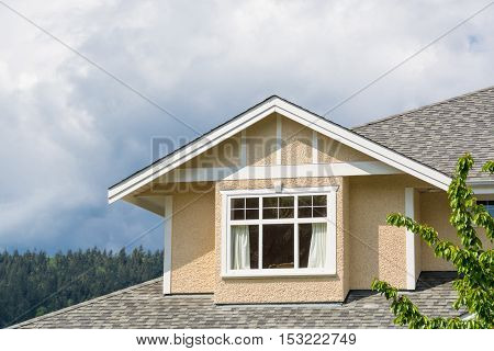 The top of the house with nice windows on cloudy sky background