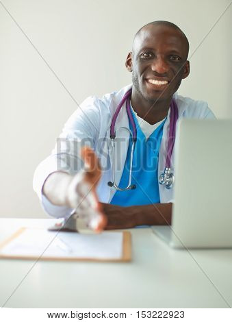 Male doctor handshake at his patient in medical office