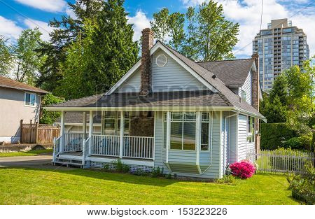 Family house with small patio and green lawn of the front yard in urban area of Vancouver