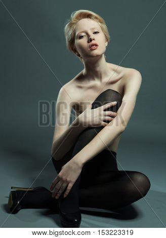 seductive woman sitting in fashion pose wearing black pantyhose
