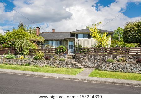 Residential house on a street in British Columbia. Family house with landscaped front yard on stone terraces